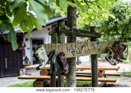 Party Label rubber boots sign wooden forest tree house Herzlich Willkommen Means Welcome made up by the photographer in his garden