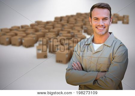 Confident delivery man standing with arms crossed against grey background