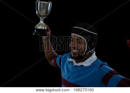 High angle view of happy rugby player holding trophy against black background