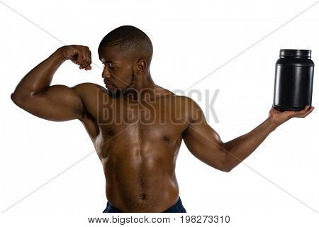 Shirtless male athlete looking at muscles while holding supplement jar against white background