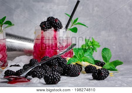 Close-up of a glass full of tasty, cold, beverage with blackberries, mint, lemon, and cubes of ice on a light gray background. The cocktail with black straw and berries. Copy space.