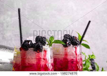 A close-up picture of two glasses full of tasty, cold and icy drinks with fragrant mint, ripe blackberries and sweet jam on a gray blurred background. Refreshing beverages with black straws.