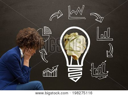 Digital composite of Woman sitting next to light bulb with crumpled paper ball and business graphics in front of blackboa