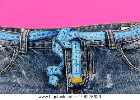 Blue jeans with blue measure tape instead of belt. Healthy lifestyle and dieting concept. Top part of denim trousers isolated on pink background. Close up of jeans with measure tape around waist.