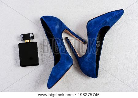 Female Shoes In Dark Blue Color And Black Perfume Bottle