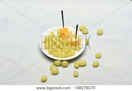 White Grapes On Plate And Around It With Cheese Skewers