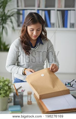 Female entrepreneur opening envelope with business correspondence