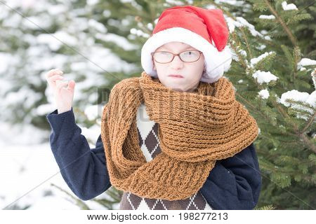 small christmas angry boy or cute nerd kid in glasses sweater fashionable knitted scarf and red santa claus hat in winter outdoor at green fir tree with snow on natural background