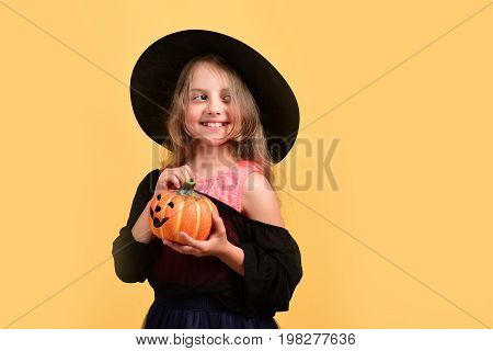 Halloween And Autumn Holiday Concept. Girl With Carved Orange Pumpkin