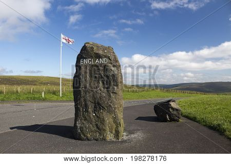 English flag rock with England painted on it and information board marking the Scottish - English Border Northumberland United Kingdom