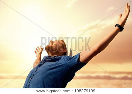 Happy man raising his arms up  against view of beach during sunset