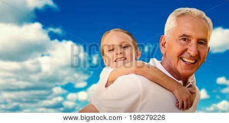 Grandfather holding his grandchild on his back against scenic view of blue sky