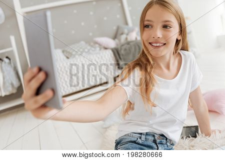 Saying cheese. Radiant girl wearing casual attire sitting on a faux fur carpet and grinning wildly while posing for photos at home.