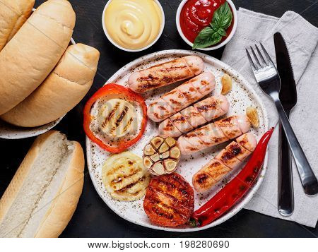 Top view of chicken homemade sausages, buns bread, sauces ketchup and mustard on black background. Grilled sausages and grilled vegetables in craft trendy plate. Homemade hotdogs.