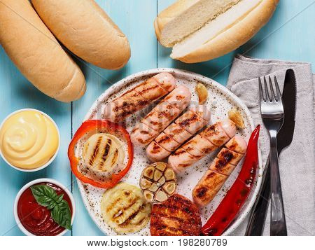 Top view of chicken homemade sausages, buns bread, sauces ketchup and mustard on blue wooden background. Grilled sausages and grilled vegetables in craft trendy plate. Homemade hotdogs.