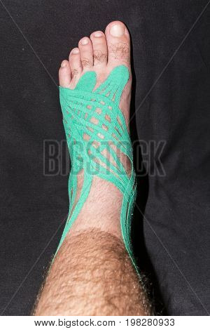 Left Foot Injury Treated Elastic Therapeutic Tape.