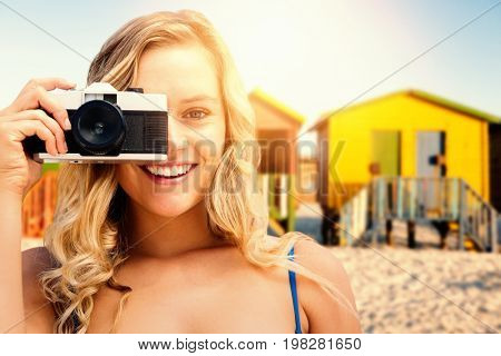 Smiling girl taking a photo against multi colored huts on sand against clear sky