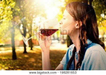 Woman drinking red wine against defocused image of trees growing at park