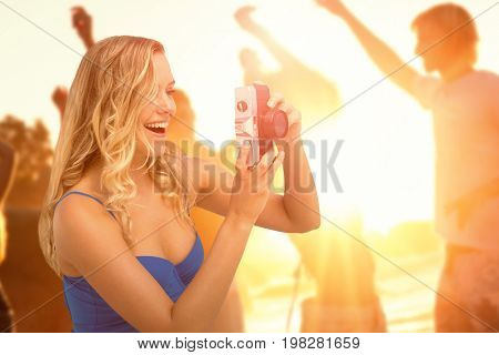 Smiling girl taking a photo against friends enjoying at beach