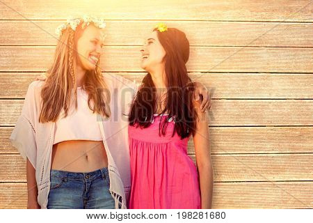 Beautiful women with a flower crown arm in arm   against wooden surface with planks