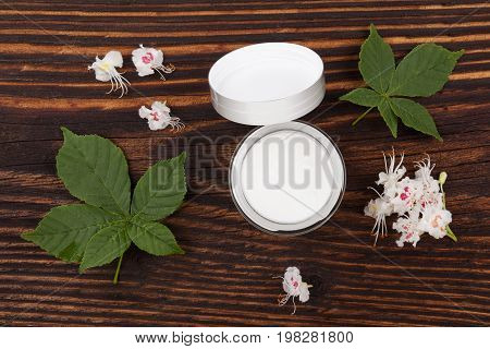 Natural organic cosmetics. Chestnut moisturizer creme on wooden table with leaves and flowers.