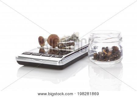 Fresh magic mushrooms gelcaps on digital scale dried mushrooms in glass jar isolated on white background.Alternative medicine.