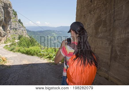 Tourist in the mountains in the artificial tunnel. Eco tourism and healthy lifestyle concept. Young hiker girl. with backpack. Active hiker