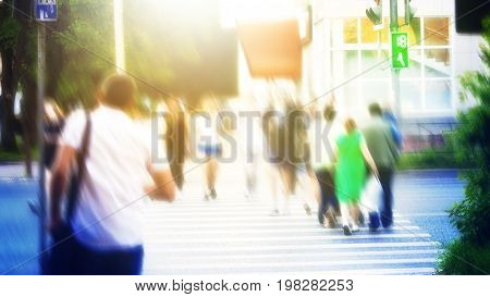 People cross the road to the green light of a traffic light blurred background