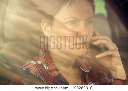 Worried woman talking on mobile phone in car concerned adult caucasian female person during telephone conversation
