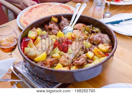 traditional croatian food peka with mix meat, vegetables and wine