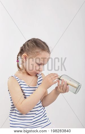 Cute little girl with message in glass bottle isolated on white background. Pirate sailor and seaman concept.