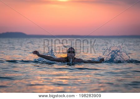 Silhouette portrait of female swimmer swimming in ocean at sunset over sea. Water sport and healthy lifestyle concepts.