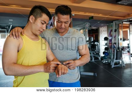 Gym visitor showing information on fitness tracker to his instructor