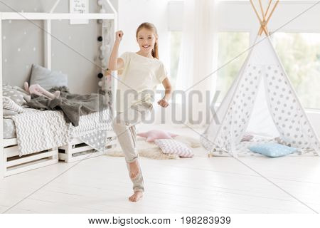 No time for worries. Joyful female youngster wearing casual attire having fun and grinning widely into the camera while spending leisure time in her bedroom.