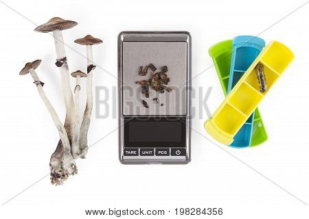 Magic mushrooms medicine microdosing pillbox digital scale isolated on white background from above. Psychedelic psilocybin medicine natural remedy.