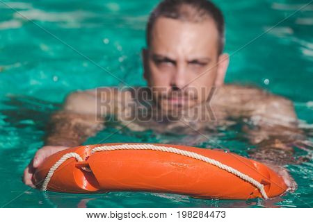 Swimmer using lifebuoy in water. Lifesaving concept