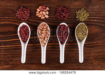 Various fresh legumes in spoon on wooden table top view. Vegetarian and vegan healthy eating.