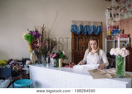 woman florist making bouquet of flowers and cutting off the wrapping paper indoor. Female florist preparing bouquet with tulip in flower shop.