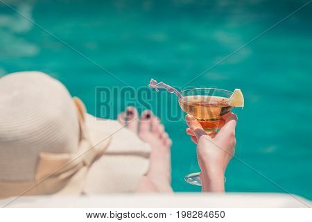 Rear view of female lying in sunbed and holding glass of copacabana cocktail at the poolside