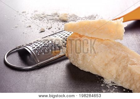 Fresh grated Parmesan cheese with grater. Luxurious parmigiano cheese background. Traditional italian cheese eating.