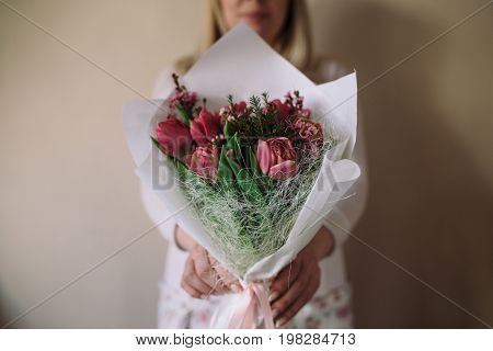 woman florist making bouquet of flowers indoor. Female florist holding bouquet with tulip in flower shop.
