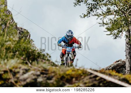 Magnitogorsk Russia - July 21 2017: man rider downhill bicycle on a mountain trail during National championship downhill
