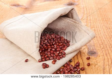 Chinese Red Mung Beans in cloth on wooden table. Healthy legumes eating.