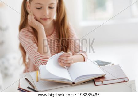 Homework is important. Calm female youngster focusing on her home assignment and looking through her book while getting ready for school.