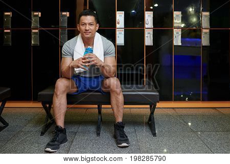 Malaysian gym trainer with water bottle sitting on bench in locker room
