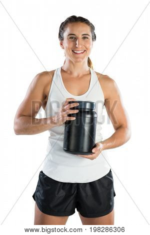 Portrait of smiling female athlete holding supplement jar while standing against white background