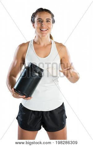 Portrait of smiling female athlete taking supplement powder while standing against white background