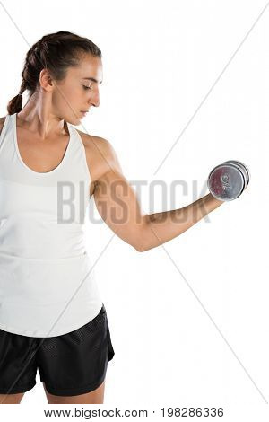 Young female rugby player lifting dumbbell while against white background