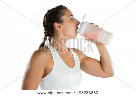 Female athlete drinking energy drink while standing against white background