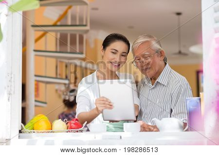 Cheerful father and adult daughter watching something interesting on tablet computer when drinking tea